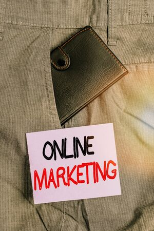 Writing note showing Online Marketing. Business concept for leveraging web based channels spread about companys brand Small wallet inside trouser front pocket near notation paper