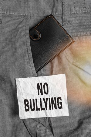 Text sign showing No Bullying. Business photo showcasing stop aggressive behavior among children power imbalance Small little wallet inside man trousers front pocket near notation paper