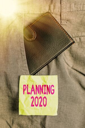 Conceptual hand writing showing Planning 2020. Concept meaning process of making plans for something next year Small wallet inside trouser front pocket near notation paper 版權商用圖片