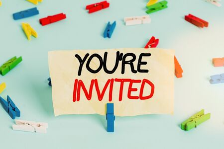 Text sign showing You Re Invited. Business photo showcasing make a polite friendly request to someone go somewhere Colored clothespin papers empty reminder blue floor background office pin