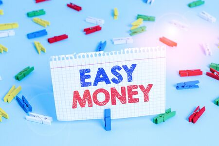 Writing note showing Easy Money. Business concept for money that is easily have and sometimes dishonestly earned Colored clothespin papers empty reminder blue floor officepin Фото со стока