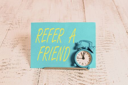 Handwriting text Refer A Friend. Conceptual photo direct someone to another or send him something like gift Mini blue alarm clock stand tilted above buffer wire in front of notepaper