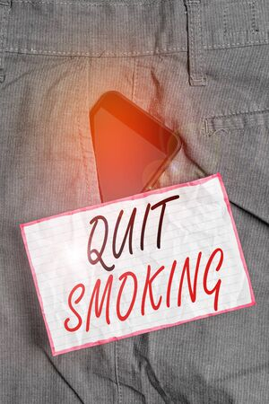 Text sign showing Quit Smoking. Business photo showcasing process of discontinuing tobacco smoking or cessation Smartphone device inside formal work trousers front pocket near note paper Imagens