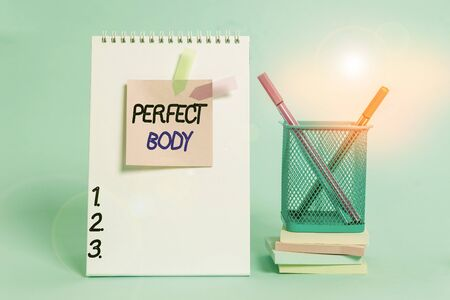 Text sign showing Perfect Body. Business photo showcasing Having a body that is dreamily in shape and in healthy state Spiral notebook sticky note banners stacked pads pens holder pastel back Standard-Bild - 143166598