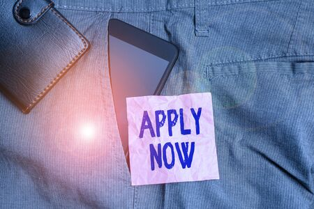 Text sign showing Apply Now. Business photo showcasing request something officially in writing or by sending in form Smartphone device inside trousers front pocket with wallet and note paper