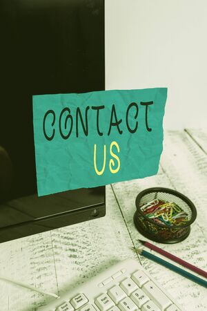 Conceptual hand writing showing Contact Us. Concept meaning Term used to describe reaching out with the business or demonstrating Note paper taped to black screen near keyboard stationary