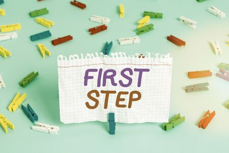 Conceptual hand writing showing First Step. Concept meaning The first of a series of actions Act of starting something Colored clothespin paper empty reminder blue floor officepin