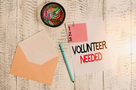 Word writing text Volunteer Needed. Business photo showcasing asking demonstrating to work for organization without being paid Envelope sheet paper sticky note ballpoint clips holder wooden background