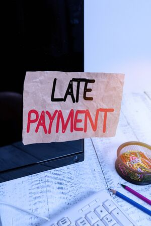 Text sign showing Late Payment. Business photo showcasing payment made to the lender after the due date has passed Note paper taped to black computer screen near keyboard and stationary