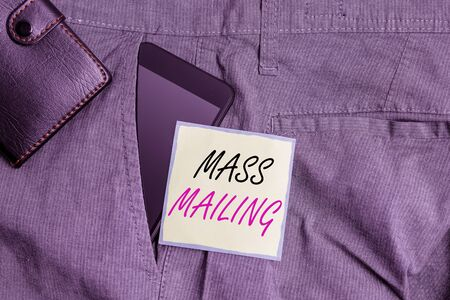 Text sign showing Mass Mailing. Business photo text act of sending the same email to a large group of showing Smartphone device inside trousers front pocket with wallet and note paper