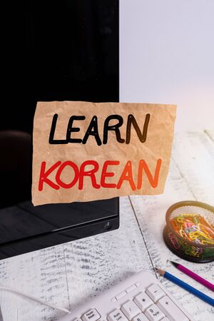 Text sign showing Learn Korean. Business photo showcasing get knowledge or skill in speaking and writing Korean language Note paper taped to black computer screen near keyboard and stationary