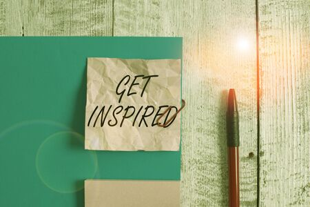 Text sign showing Get Inspired. Business photo showcasing make someone have a particular strong feeling or reaction Wrinkle paper and cardboard plus stationary placed above wooden background
