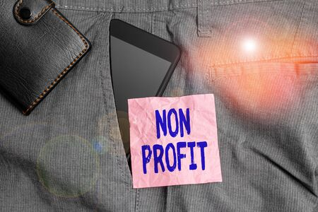 Text sign showing Non Profit. Business photo showcasing not making or conducted primarily to make profit organization Smartphone device inside trousers front pocket with wallet and note paper