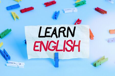 Text sign showing Learn English. Business photo showcasing gain acquire knowledge in new language by study Colored clothespin papers empty reminder blue floor background office pin