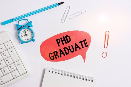Text sign showing Phd Graduate. Business photo text highest university degree that is conferred after a course Copy space on the empty note paper with pc keyboard clock and pencil on the table