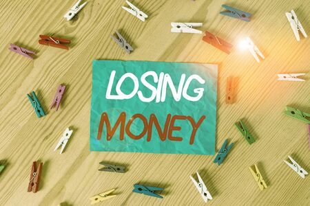 Text sign showing Losing Money. Business photo text Business that does not make a profit Spending more money Colored clothespin papers empty reminder wooden floor background office