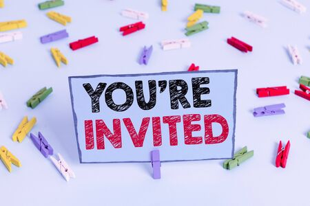 Writing note showing You Re Invited. Business concept for make a polite friendly request to someone go somewhere Colored clothespin papers empty reminder blue floor officepin