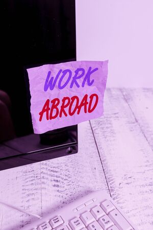 Conceptual hand writing showing Work Abroad. Concept meaning Getting a job or working in a foreign geographical area Notation paper computer monitor screen near white keyboard Banco de Imagens
