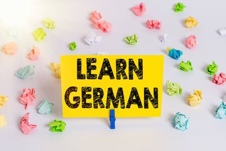 Handwriting text Learn German. Conceptual photo get knowledge or skill in speaking and writing German language Colored crumpled papers empty reminder white floor background clothespin