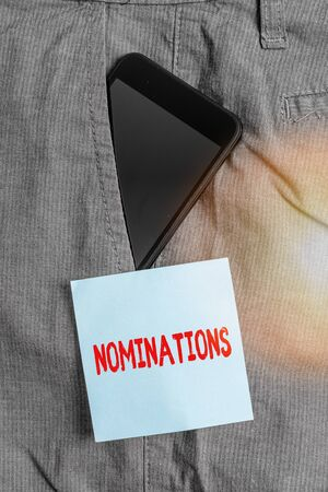 Conceptual hand writing showing Nominations. Concept meaning the act of officially suggesting someone for a job or position Smartphone device inside trousers front pocket note paper