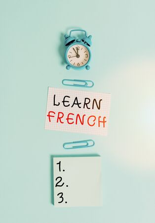 Text sign showing Learn French. Business photo text get knowledge or skill in speaking and writing French language Alarm clock squared blank paper sheet notepad clips colored background Banco de Imagens