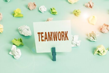 Text sign showing Teamwork. Business photo showcasing combined action of group especially when effective and efficient Colored crumpled papers empty reminder blue floor background clothespin Imagens
