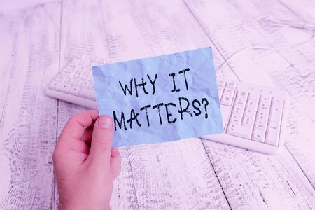 Word writing text Why It Matters Question. Business photo showcasing most important thing to be done in a situation man holding colorful reminder square shaped paper white keyboard wood floor 免版税图像 - 143222639