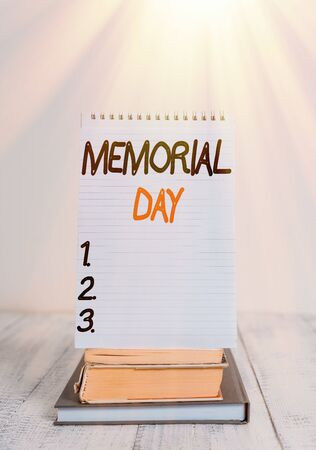 Conceptual hand writing showing Memorial Day. Concept meaning remembering the military demonstratingnel who died in service Front view stacked books spiral note book on vintage wooden table
