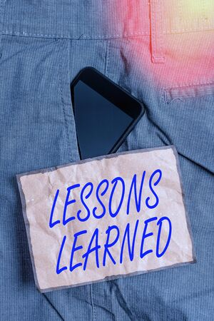 Conceptual hand writing showing Lessons Learned. Concept meaning the knowledge or understanding gained by experience Smartphone device inside trousers front pocket note paper