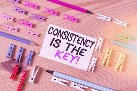 Conceptual hand writing showing Consistency Is The Key. Concept meaning by Breaking Bad Habits and Forming Good Ones Colored crumpled papers wooden floor background clothespin Foto de archivo