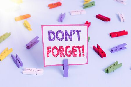 Text sign showing Dont Forget. Business photo text used to remind someone about an important fact or detail Colored clothespin papers empty reminder blue floor background office pin