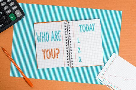 Handwriting text writing Who Are Youquestion. Conceptual photo someone asking your personal background or history Striped paperboard notebook cardboard office study supplies chart paper
