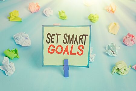 Conceptual hand writing showing Set Smart Goals. Concept meaning giving criteria to guide in the setting of objectives Colored crumpled papers empty reminder blue floor clothespin