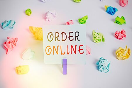 Text sign showing Order Online. Business photo showcasing activity of buying products or services over the Internet Colored crumpled papers empty reminder white floor background clothespin