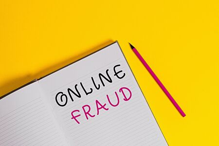 Text sign showing Online Fraud. Business photo text use of Internet services to deceive victims and steal money Open striped hard cover notebook lying pencil marker color background