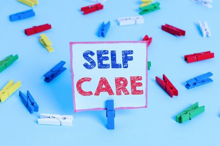 Text sign showing Self Care. Business photo text the practice of taking action to improve one own health Colored clothespin papers empty reminder blue floor background office pin Stock fotó