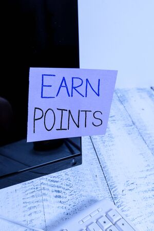 Text sign showing Earn Points. Business photo showcasing collecting scores in order qualify to win big prize Notation paper taped to black computer monitor screen near white keyboard Фото со стока