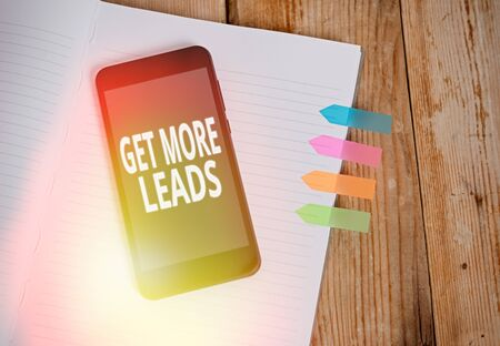 Writing note showing Get More Leads. Business concept for to have more customers and improve your target sales Striped note book colored arrow banners smartphone wooden background Stockfoto