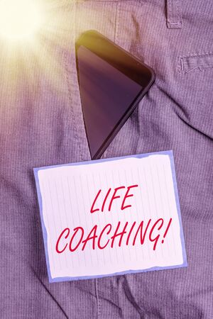 Conceptual hand writing showing Life Coaching. Concept meaning Employee employed to help showing attain their goals in career Smartphone device inside trousers front pocket note paper Stock Photo