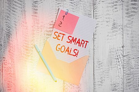 Text sign showing Set Smart Goals. Business photo text giving criteria to guide in the setting of objectives Envelope blank sheet letter paper sticky note ballpoint wooden background