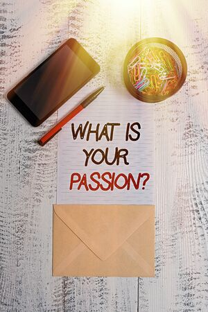 Writing note showing What Is Your Passion Question. Business concept for asking about his strong and barely controllable emotion Smartphone paper sheet clips pen envelope wooden vintage background