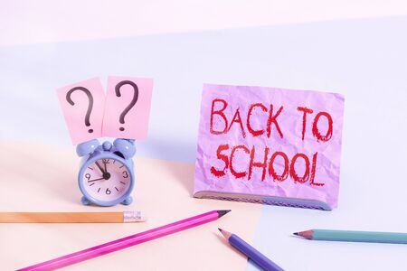 Text sign showing Back To School. Business photo showcasing is the period relating to the start of a new school year Mini size alarm clock beside stationary placed tilted on pastel backdrop 스톡 콘텐츠