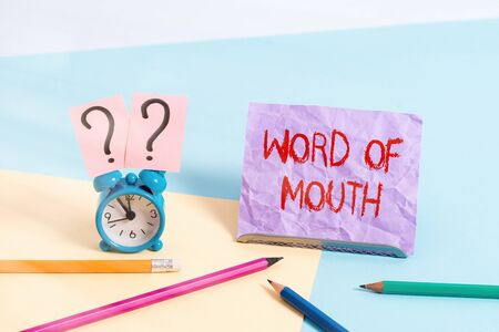 Text sign showing Word Of Mouth. Business photo showcasing information that is transmitted without being written down Mini size alarm clock beside stationary placed tilted on pastel backdrop 免版税图像