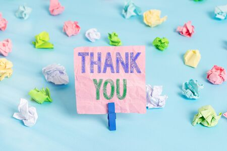 Conceptual hand writing showing Thank You. Concept meaning a polite expression used when acknowledging a gift or service Colored crumpled papers empty reminder blue floor clothespin