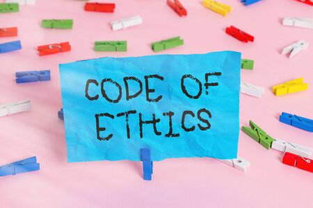 Conceptual hand writing showing Code Of Ethics. Concept meaning basic guide for professional conduct and imposes duties Colored clothespin papers empty reminder pink floor office