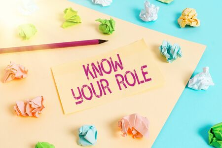 Handwriting text writing Know Your Role. Conceptual photo end acting outside who you actually are Play your position Colored crumpled papers empty reminder blue yellow background clothespin