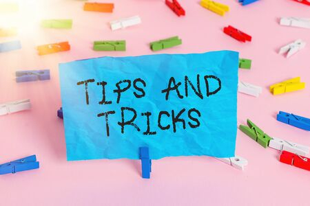 Conceptual hand writing showing Tips And Tricks. Concept meaning piece of inside facts specially in betting or investing Colored clothespin papers empty reminder pink floor office 写真素材