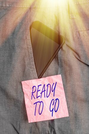 Text sign showing Ready To Go. Business photo showcasing prepared and suitable to move or to travel to another place Smartphone device inside formal work trousers front pocket near note paper 写真素材
