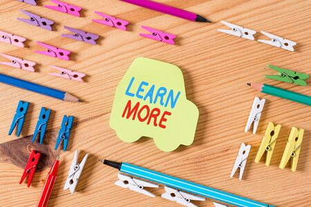 Word writing text Learn More. Business photo showcasing knowledge or skill acquired by instruction Considerable learning Colored clothespin papers empty reminder wooden floor background office