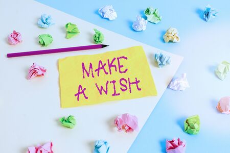 Word writing text Make A Wish. Business photo showcasing to desire a situation that is different from the one that exist Colored crumpled papers empty reminder blue yellow background clothespin Фото со стока